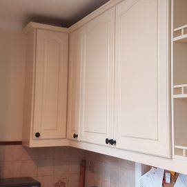 white painted cupboards and clock